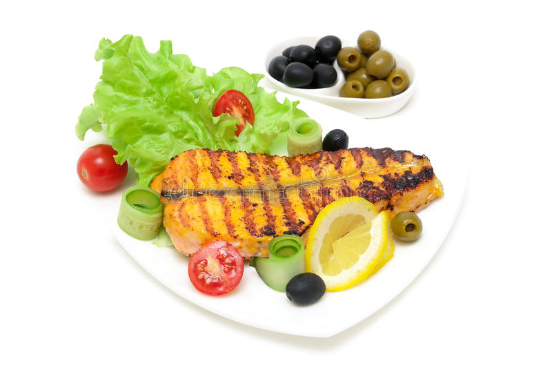 Kawałek piec łosoś z cytryną i warzywami na talerzu dalej zdjęcia stock