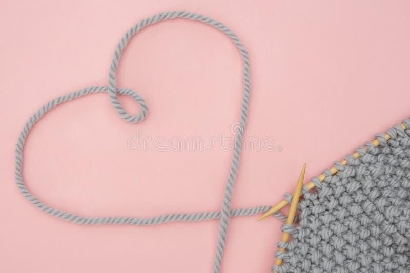 Kawałek popielata trykotowa tkanina na drewnianych igłach i niciany kierowy kształt, proces dzianie na różowym tle Pojęcie miłość zdjęcia royalty free