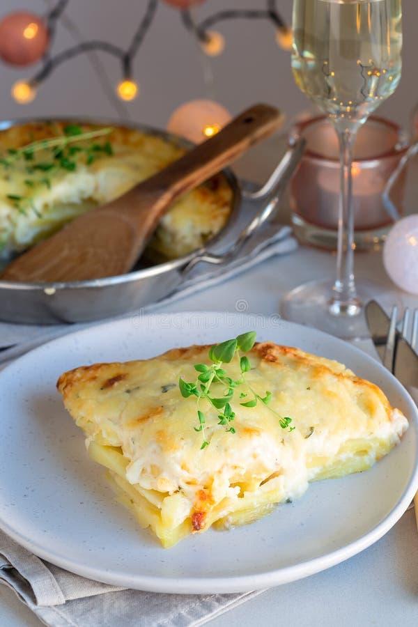 Kawałek tandetne scalloped grule lub kartoflany gratin na talerzu, zdjęcia royalty free