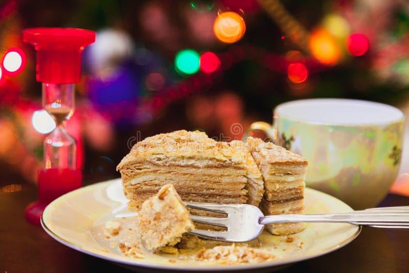 Kawałek tort kłama na talerzu przeciw tłu Bożenarodzeniowy ligh zdjęcie royalty free