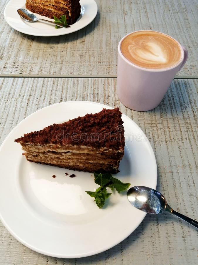 Kawałek tort na białym talerzu na stole w kawiarni blisko filiżanka kawy cappuccino zdjęcie royalty free