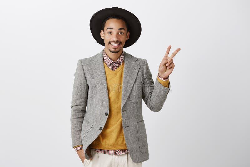 Kawałka mężczyzna Portret atrakcyjny życzliwy projektant mody w eleganckim stroju, kapeluszowym pokazuje zwycięstwie i v znaku po zdjęcia stock