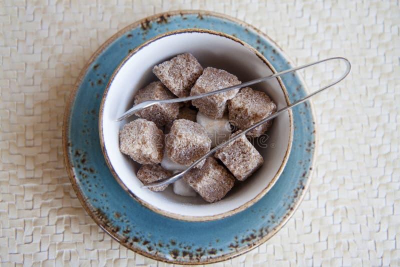 Kawałki biel i brown cukier w cukierniczce z cukrowymi tongs zdjęcie royalty free