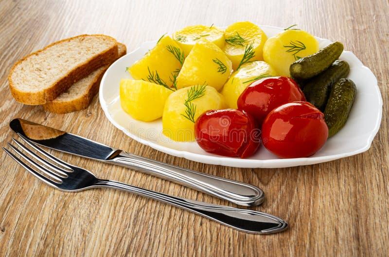 Kawałki chleb, naczynie z piec grulą, marynowani pomidory, korniszony, koper, nóż i rozwidlenie na stole, fotografia stock