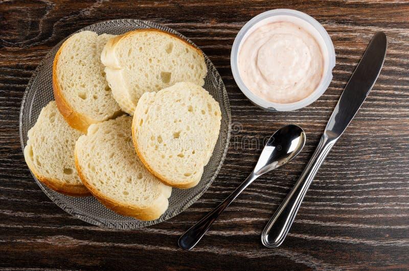 Kawałki chleb w talerzu, słój z krill pastą, łyżka, nóż na drewnianym stole Odg?rny widok obraz royalty free