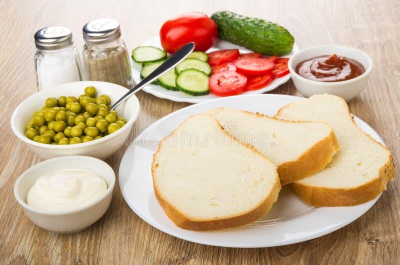 Kawałki chleb, zieleni grochy, plasterki warzywa, kumberlandy, sól obrazy stock