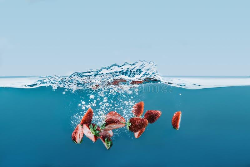Kawałki dojrzałe truskawki spada w wodę z pluśnięciami zdjęcie stock