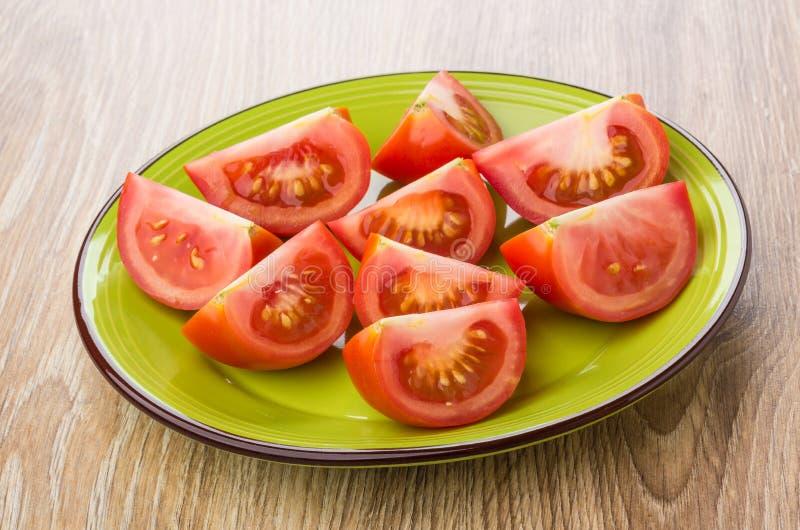 Kawałki dojrzali czerwoni pomidory w zieleń talerzu na stole obrazy royalty free