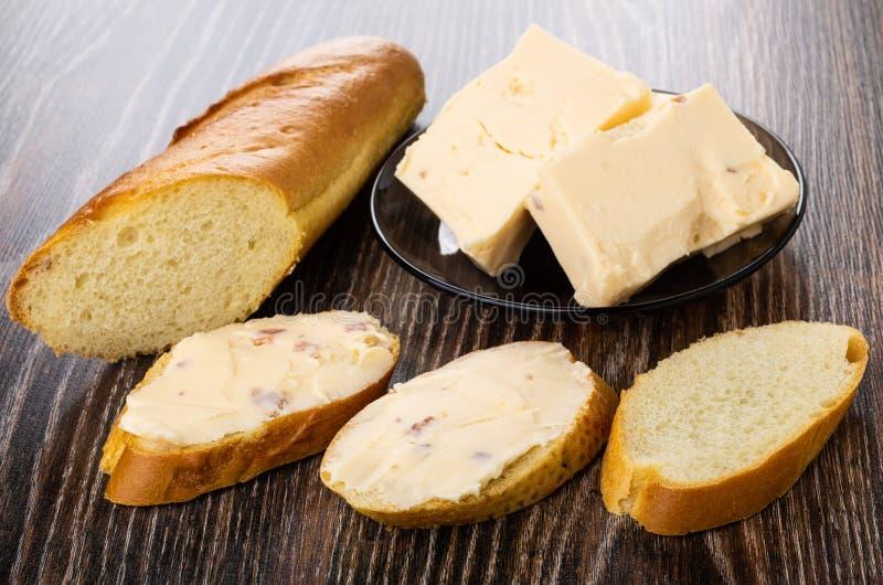 Kawałki rozciekły ser z bekonem w talerzu, chleb, ściskają z serem na stole zdjęcie stock