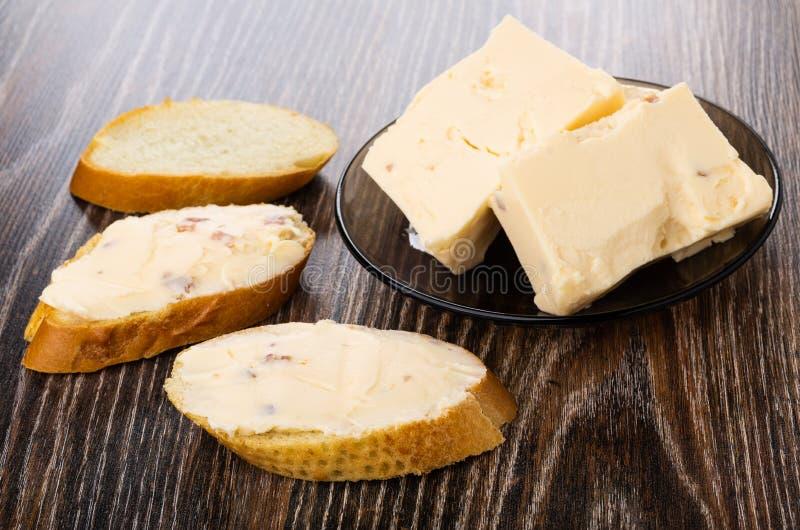 Kawałki rozciekły ser z bekonem w talerzu i kanapkach z serem na stole obrazy royalty free