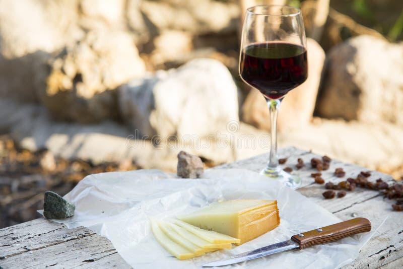 Kawałki ser i rodzynki z czerwonego wina szkłem na starym drewnie fotografia royalty free