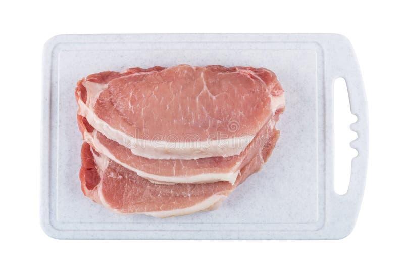 Kawałki surowa wieprzowina na tnącej desce odizolowywającej na bielu fotografia royalty free