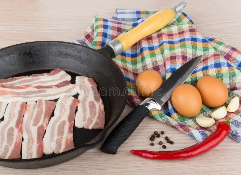 Kawałki surowy bekon w smażyć nieckę pieprzą, jajka, czosnek, zdjęcie royalty free