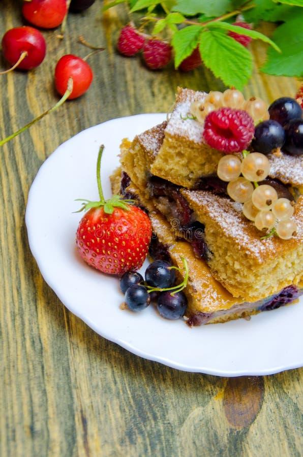 Kawałki tort z jagodami i świeżymi truskawkowymi jagodami na drewnianym tle porzeczkowymi i czereśniowymi zdjęcia royalty free