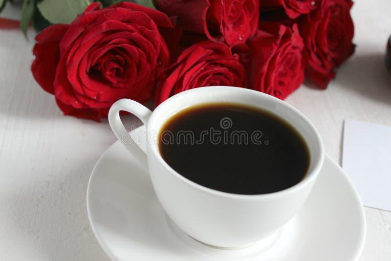 Kawa życie i róże, wciąż Czarna kawa w białej filiżance z spodeczkiem na stole, bukiet czerwone róże fotografia stock