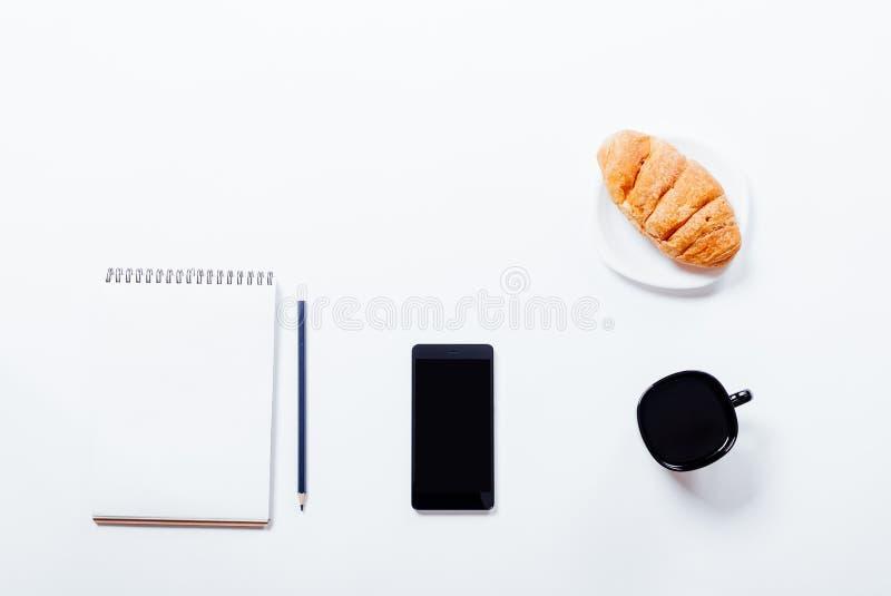 Kawa, croissant, hełmofony, telefon komórkowy i notatnik na wh, obraz stock