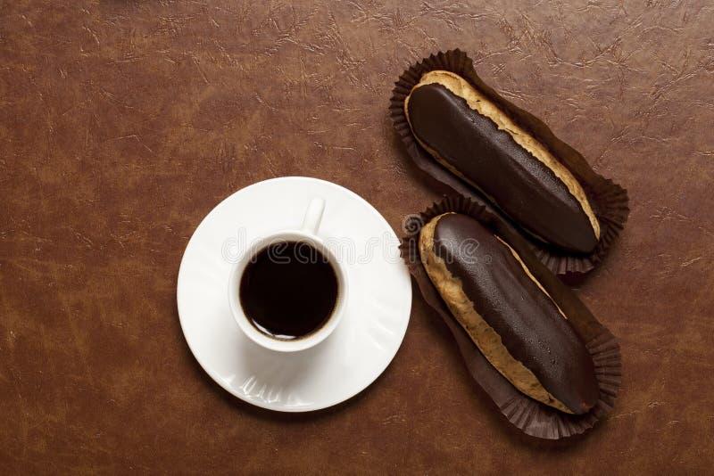 Kawa, czekoladowy Eclair, kawa w białej filiżance, biały spodeczek na brązu stole, Eclair na papieru stojaku zdjęcia royalty free