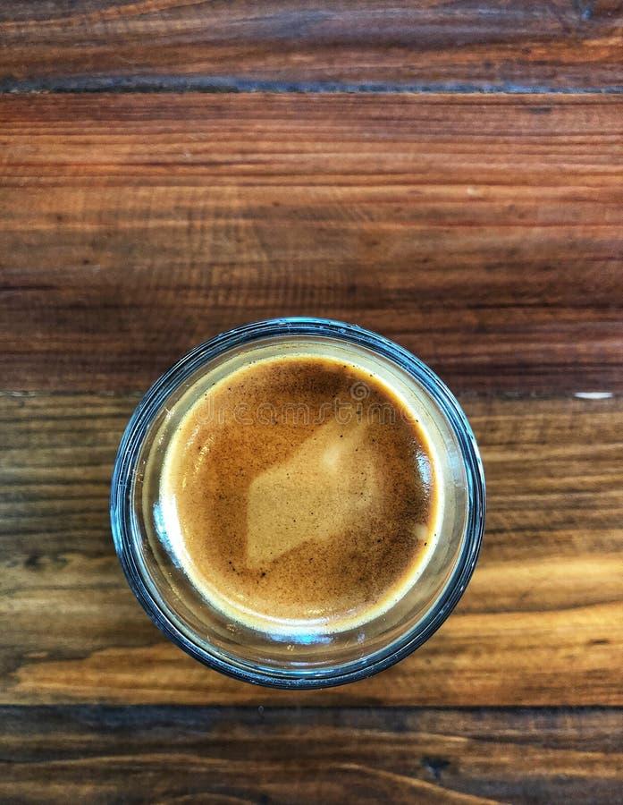 Kawa espresso strzał w szkle na rocznika drewnianym stole, fotografia stock