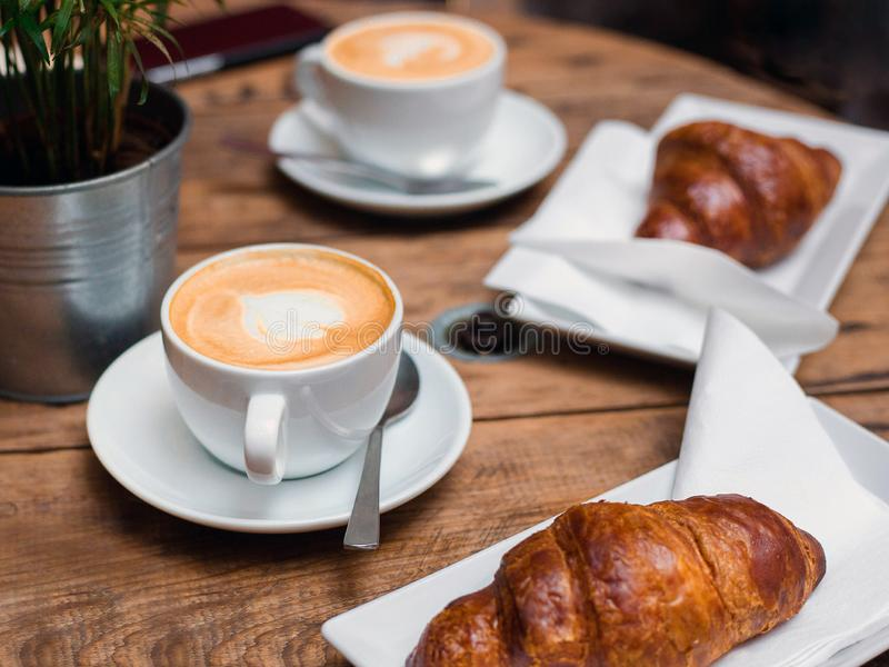 Kawa i croissant dla śniadaniowej Cukiernianej kultury Croissants z dwa filiżanek małym cappuccino z obrazkiem, odgórny widok zdjęcie stock