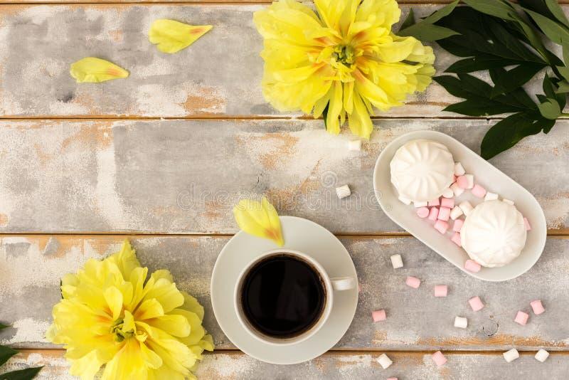 Kawa i marshmallows na drewnianym tło składzie z kwiatami zdjęcie royalty free