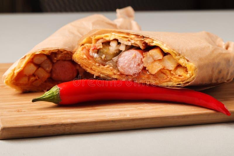 Kawa i Shawarma kiełbasa w lavash z grulami, ogórkami i kumberlandem na drewnianej desce na szarym tle, zdjęcia royalty free