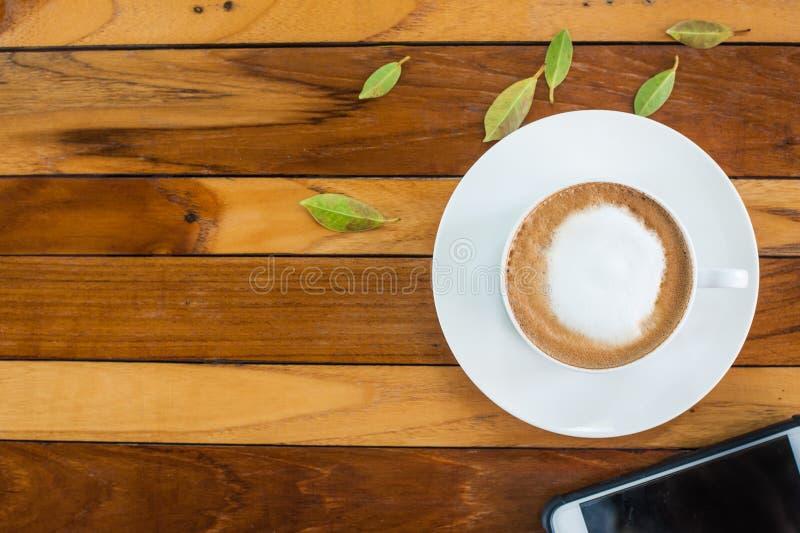 Kawa i telefon komórkowy na drewnianym stole obrazy royalty free