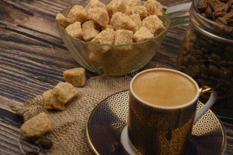 Kawa, kawałki brązowego cukru w miseczce cukrowej, ziarna kawy w szklanym słoiku na drewnianym tle obraz stock