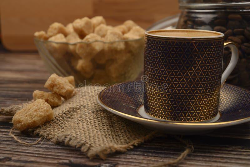 Kawa, kawałki brązowego cukru w miseczce cukrowej, ziarna kawy w szklanym słoiku na drewnianym tle fotografia stock
