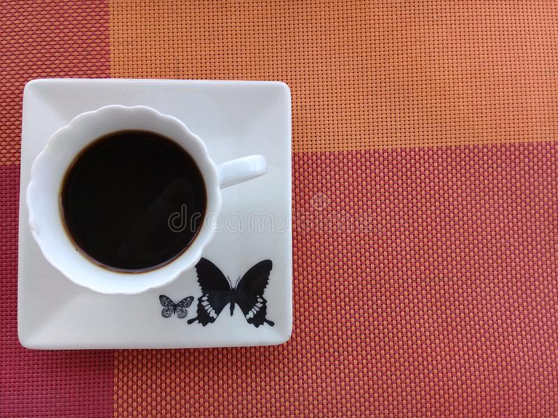 Kawa na g?rze spodeczka z motylim projektem fotografia stock