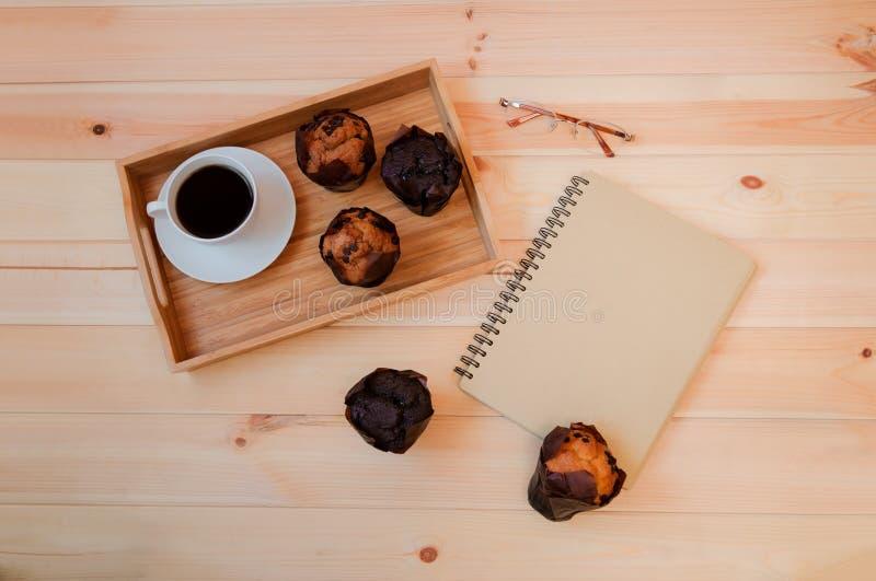 Kawa, pusty notatnik i słodka bułeczka na drewnianym tle, zdjęcie stock