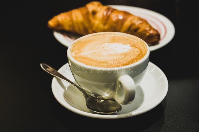 Kawa relaksuje czas Cappuccino z croissant na czarnym tle zdjęcie royalty free
