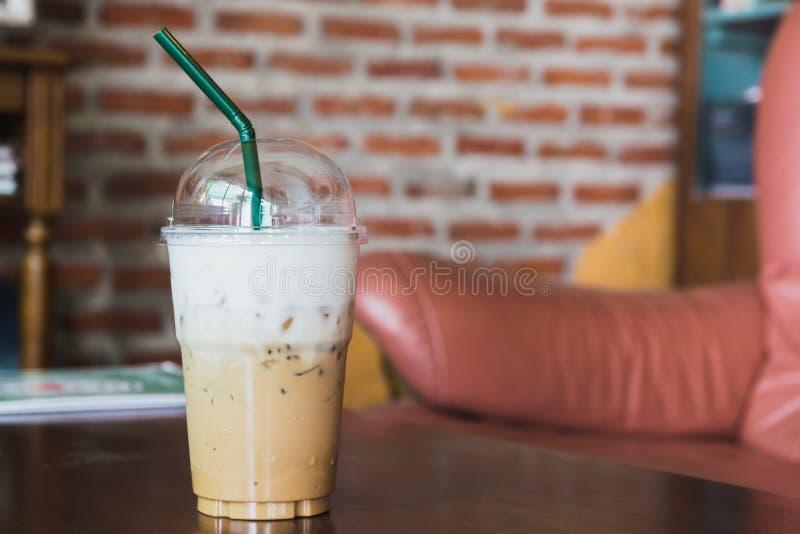 Kawa w plastikowym szkle na drewnianym stole przy żywym pokojem zdjęcia royalty free