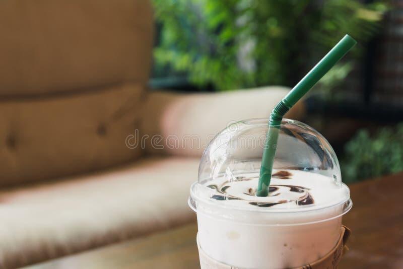 Kawa w plastikowym szkle na drewnianym stole przy żywym pokojem obrazy stock