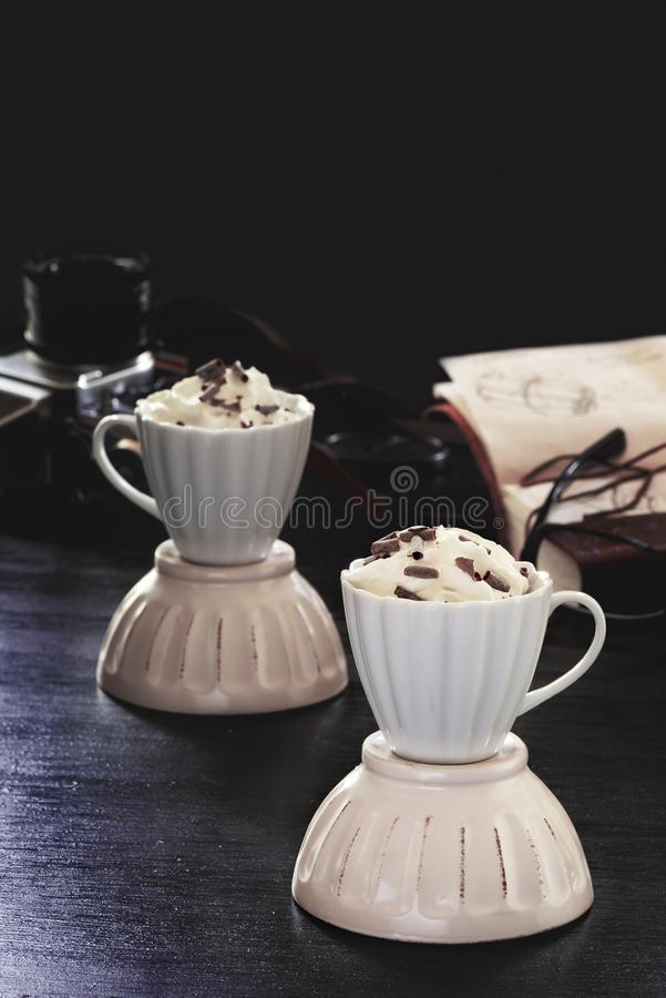 Kawa z kwa?n? ?mietank? i czekolad? na drewnianym tle obrazy stock