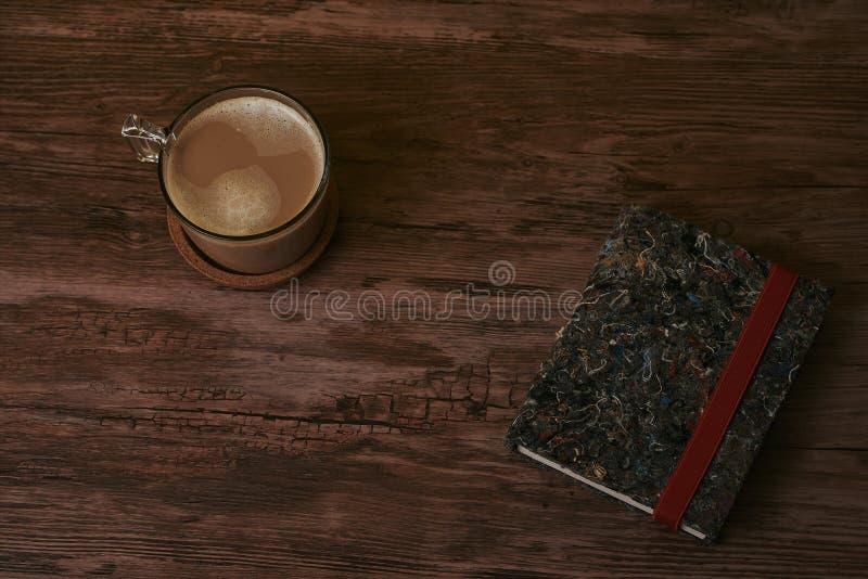 Kawa z mlekiem i książkami na brązu drewnianym stole obrazy stock