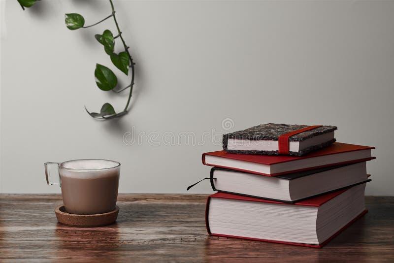 Kawa z mlekiem i książkami na brązu drewnianym stole zdjęcia royalty free