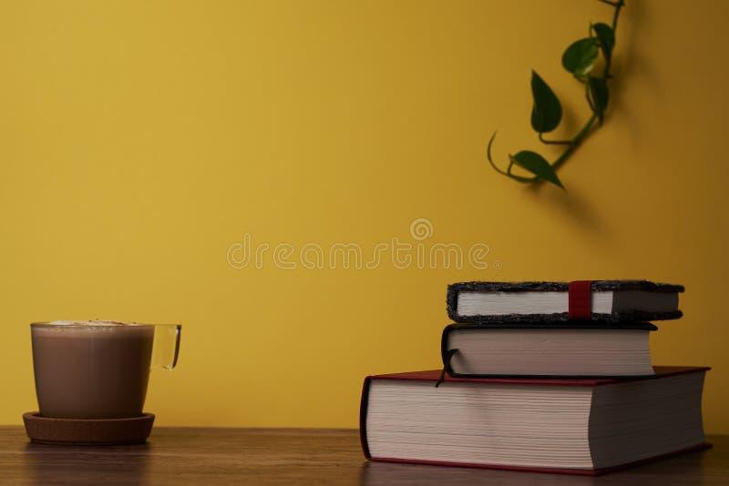Kawa z mlekiem i książkami na brązu drewnianym stole fotografia royalty free