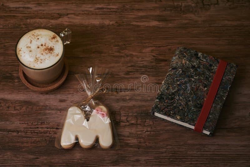 Kawa z mlekiem i książkami na brązu drewnianym stole zdjęcia stock