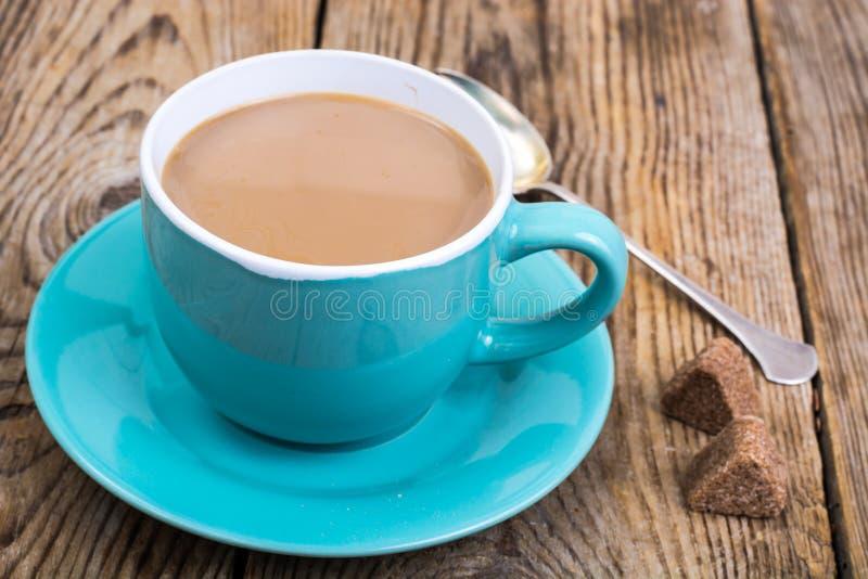 Kawa z mlekiem w błękitnej filiżance, kawałki cukier zdjęcie stock