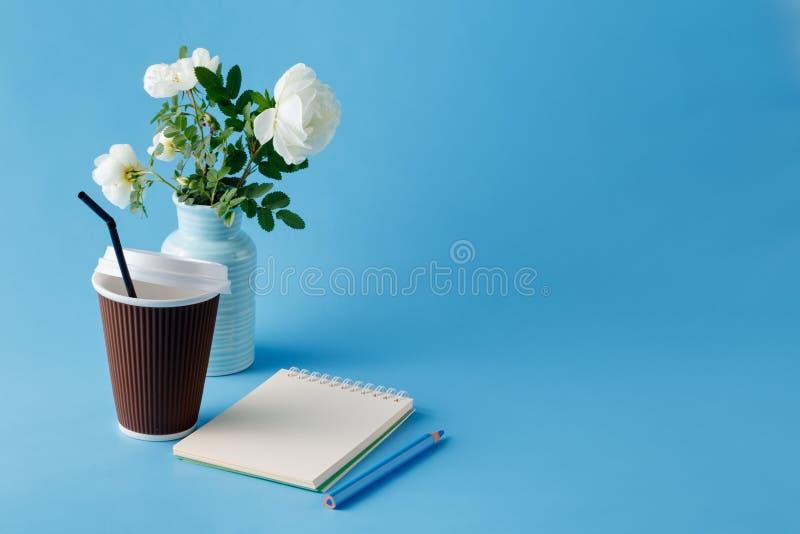 Kawa z notepad i kwiatami obrazy stock