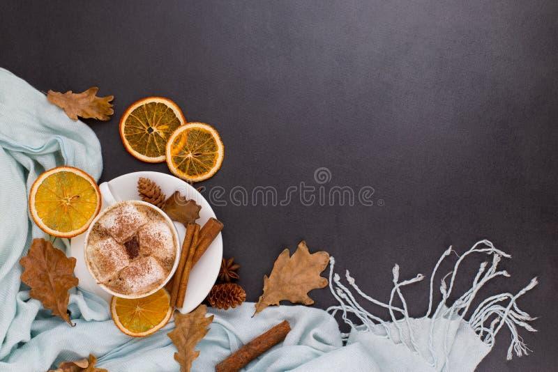 Kawa z piankami, kakao, chustką, liśćmi, suszonymi pomarańczami, przyprawami, na szarym tle Pyszny gorący napój jesienny, rano fotografia stock