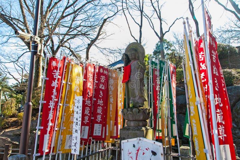 KAWAGOE, SAITAMA prefektura JAPONIA, LUTY, - 3, 2016: Antyczna Buddha statua i kolorowa flaga przy Kitain ?wi?tyni? zdjęcie royalty free