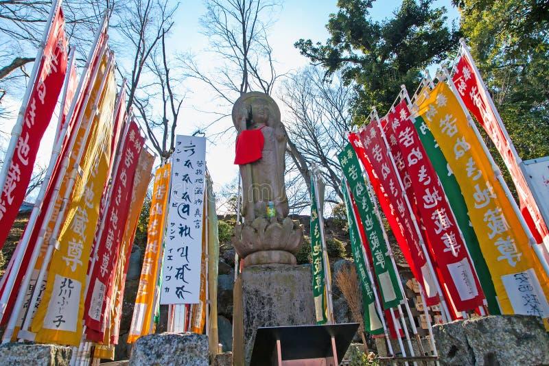 KAWAGOE, SAITAMA prefektura JAPONIA, LUTY, - 3, 2016: Antyczna Buddha statua i kolorowa flaga przy Kitain ?wi?tyni? obrazy stock