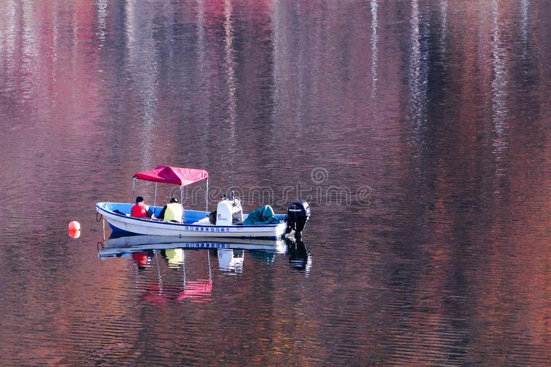 Fishing boat on autumn lake stock image