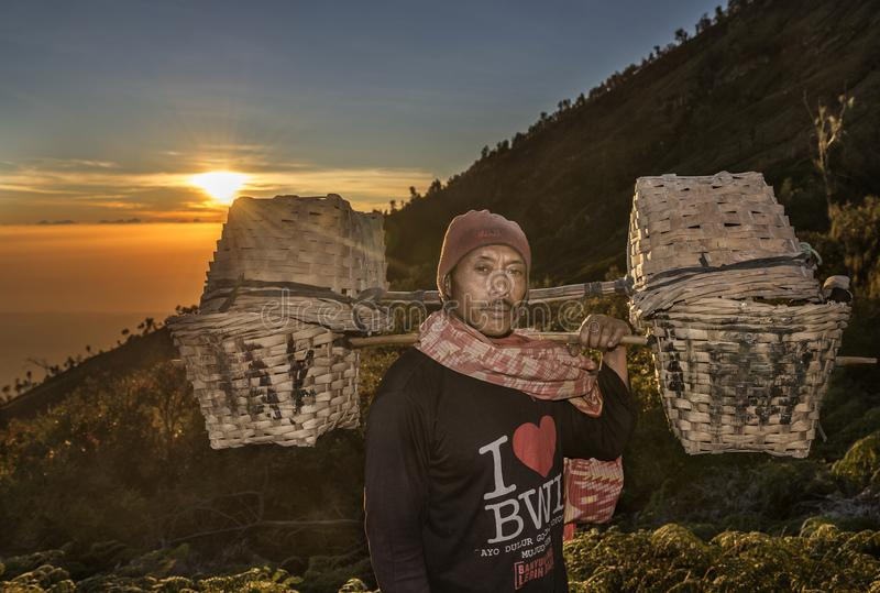 Kawah伊真火山运载他的篮子对开采的区域早晨,印度尼西亚的硫磺矿工 免版税库存照片