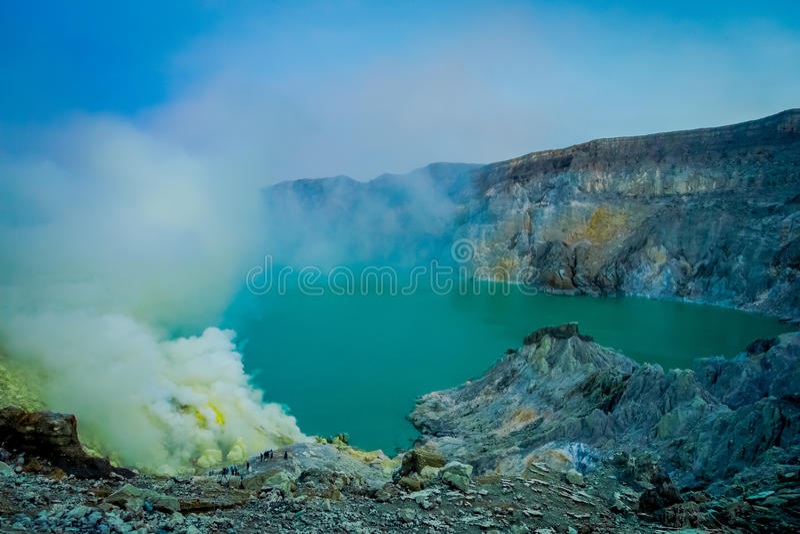 KAWEH伊真火山,印度尼西亚:有工作在火山的火山口湖,壮观的自然旁边的矿工的硫磺矿好的概要 图库摄影