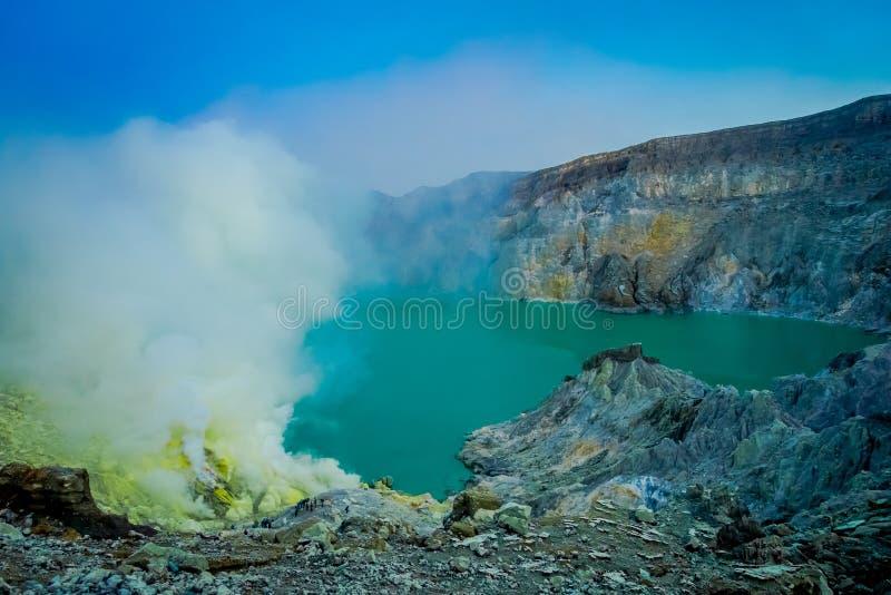 KAWEH伊真火山,印度尼西亚:有工作在火山的火山口湖,壮观的自然旁边的矿工的硫磺矿好的概要 免版税库存图片
