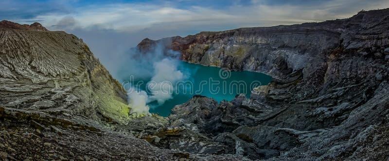 KAWEH伊真火山,印度尼西亚:有粗砺的山峭壁的火山的火山口湖,巨大自然概念壮观的概要 免版税库存照片
