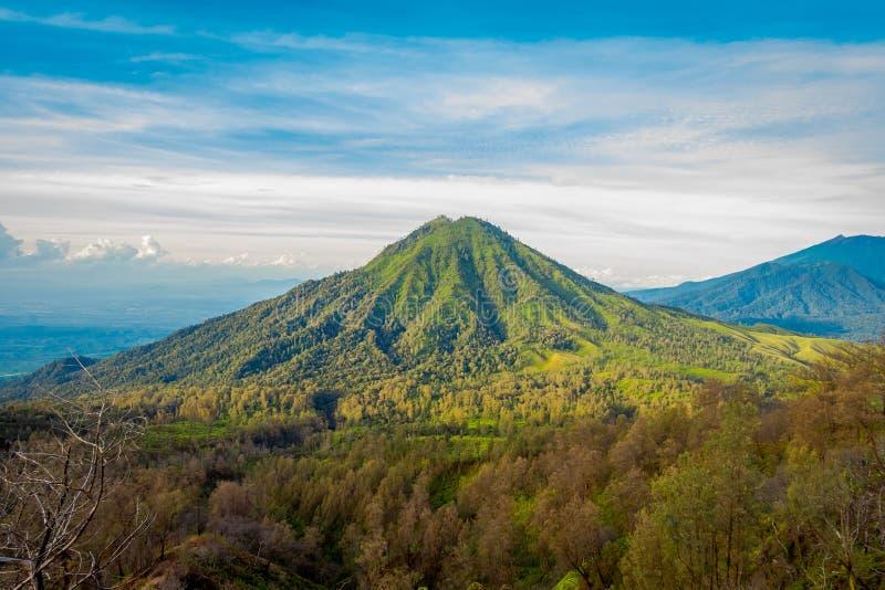 KAWEH IJEN, INDONESIEN: Härligt skott av landskapet för hög höjd med gröna berg i avståndet royaltyfri foto