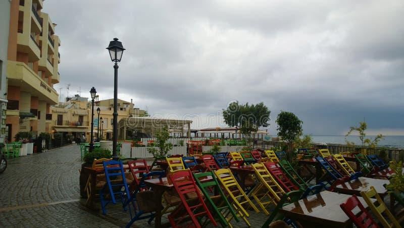 Kawiarnia z kolorowymi krzesłami na deptaku w centre Rethymnon w chmurzącej dżdżystej pogodzie obraz stock